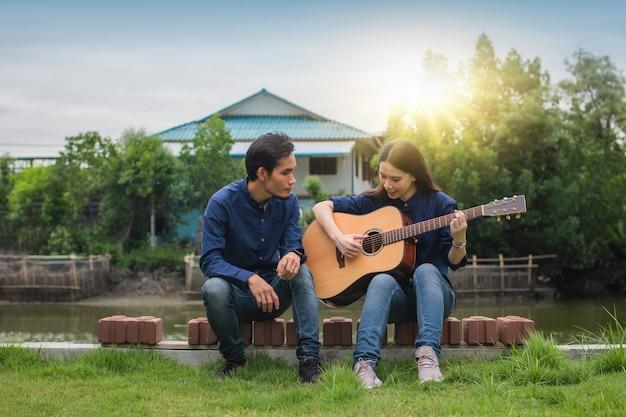 Casal familiar tocando violão no jardim em casa
