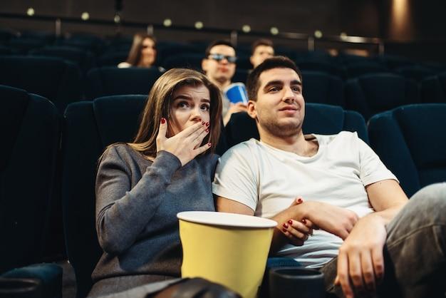 Casal fascinado assistindo o filme no cinema