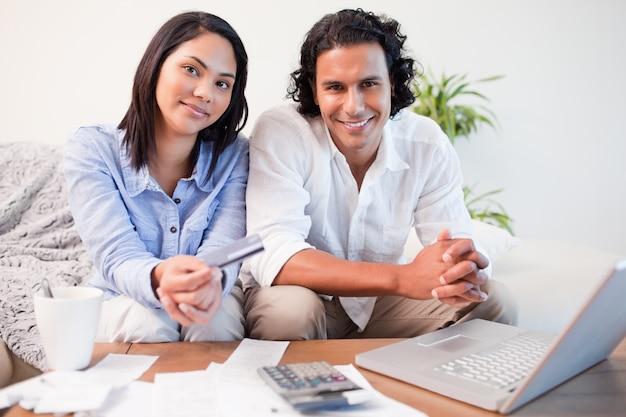 Casal fazendo banca online na sala de estar