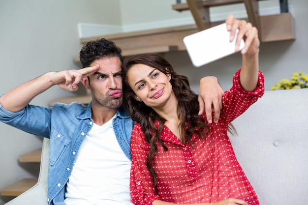 Casal fazendo caretas enquanto estiver tirando o auto-retrato