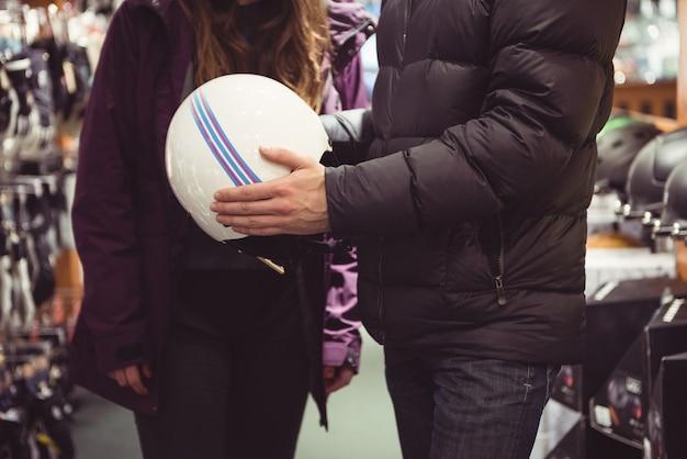 Casal fazendo compras em uma loja de capacetes