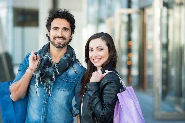 Casal fazendo compras em uma rua urbana.
