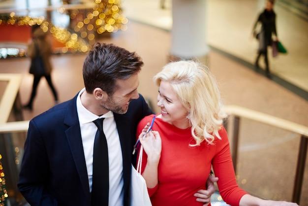 Casal fazendo compras na escada rolante do shopping