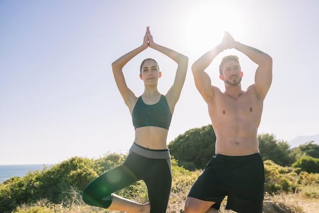 Casal fazendo exercícios de ioga ao sol