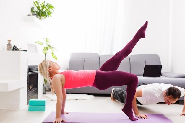 Casal fazendo exercícios em casa. conceito de ioga.