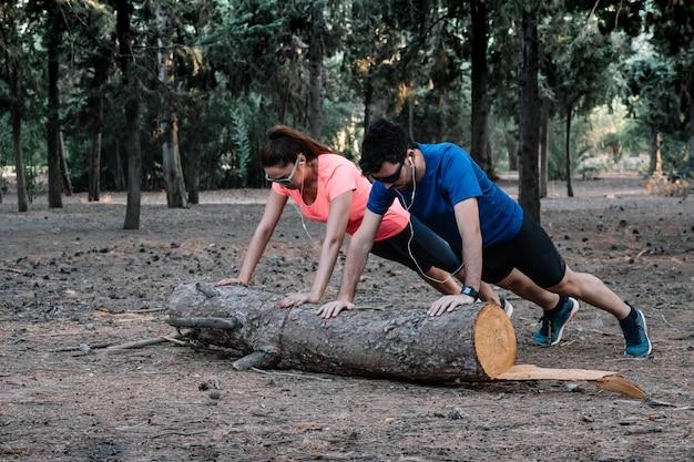 Casal fazendo flexões em um log em um parque