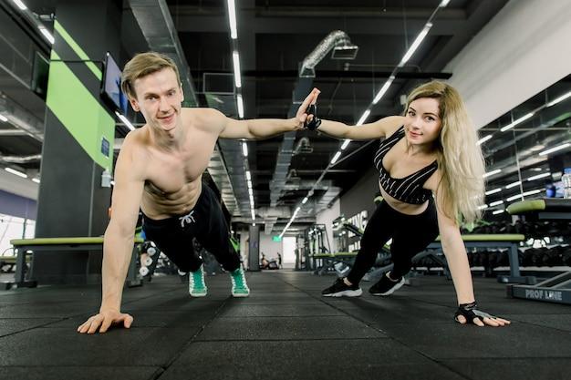 Casal fazendo flexões no treinamento no ginásio. casal desportivo fazendo flexões e dando mais cinco. interior do ginásio.
