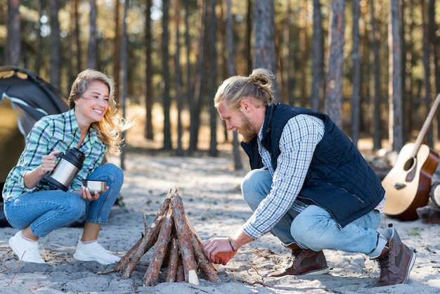 Casal fazendo fogueira