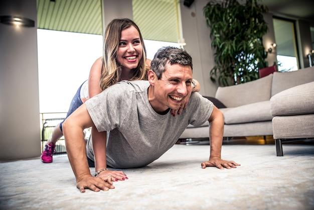 Casal fazendo marca fitness na sala de estar em casa