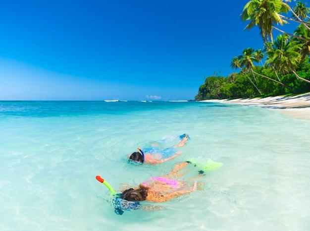 Casal fazendo mergulho com snorkel na costa