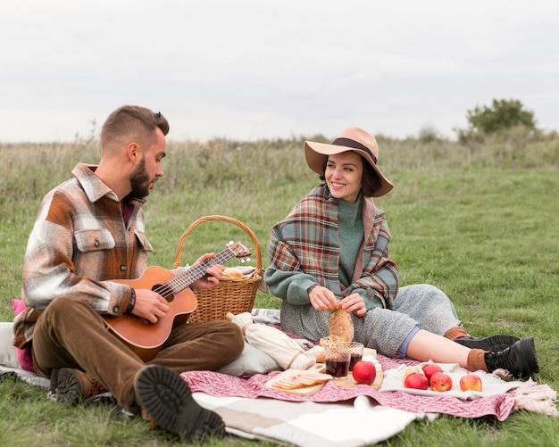 Casal fazendo piquenique na natureza Foto Premium