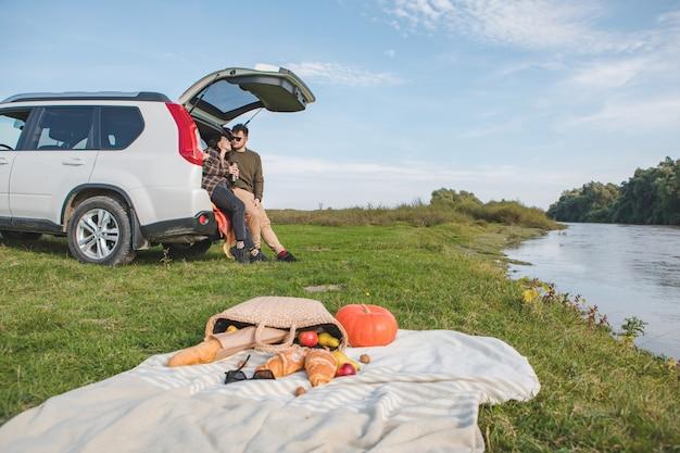 Casal fazendo piquenique na praia do rio outono dia quente cópia espaço