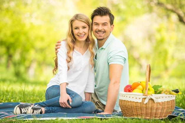 Casal fazendo piquenique no gramado no parque de verão.