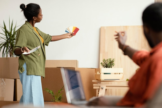 Casal fazendo planos para reformar a casa usando laptop e paleta de cores