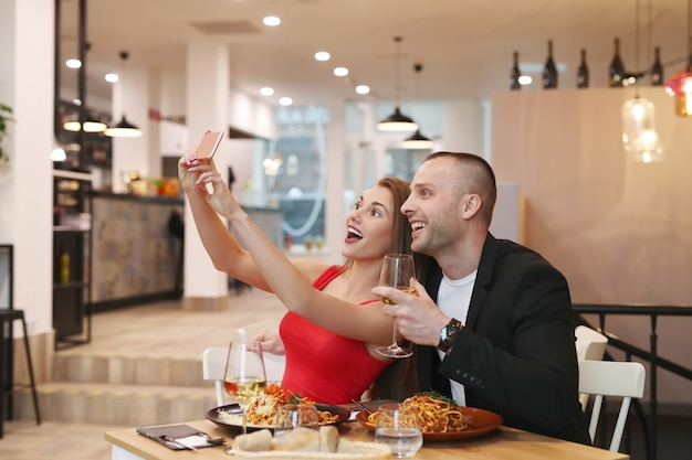 Casal fazendo selfie no restaurante