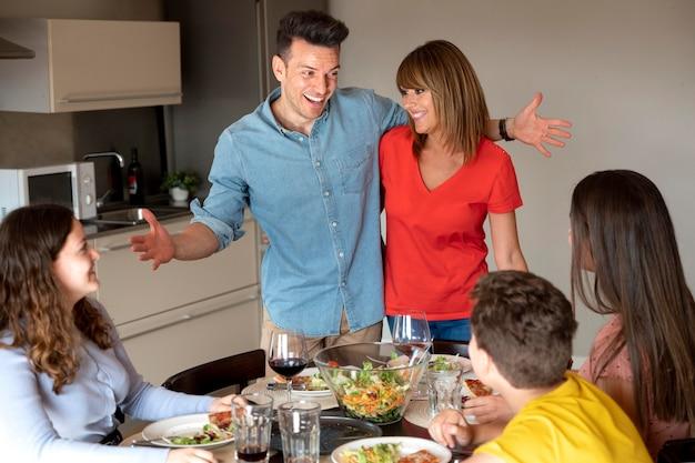 Casal fazendo um anúncio no jantar rodeado pela família