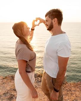 Casal fazendo um coração com os dedos ao pôr do sol