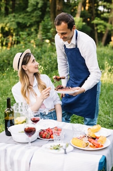 Casal fazendo um piquenique romântico na natureza