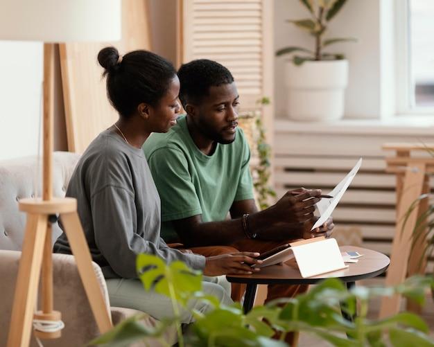 Casal fazendo um plano usando tablet para redecorar a casa