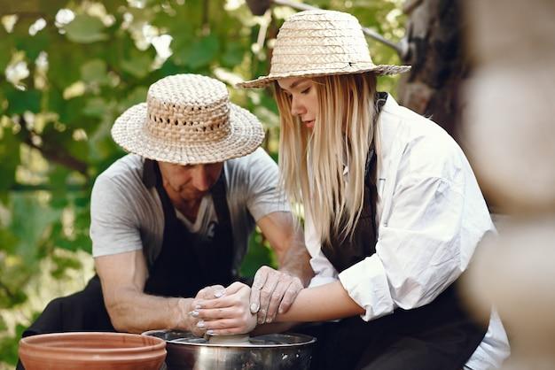 Casal fazendo um vaso com argila
