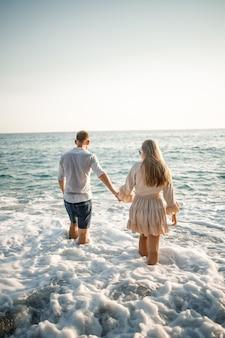 Casal feliz à beira-mar. amantes da lua de mel. homem e mulher na ilha. lindo casal se divertindo à beira-mar. casal feliz de férias. homem e mulher à beira-mar.