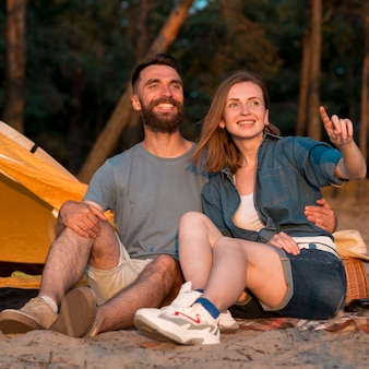Casal feliz a desviar o olhar por tenda