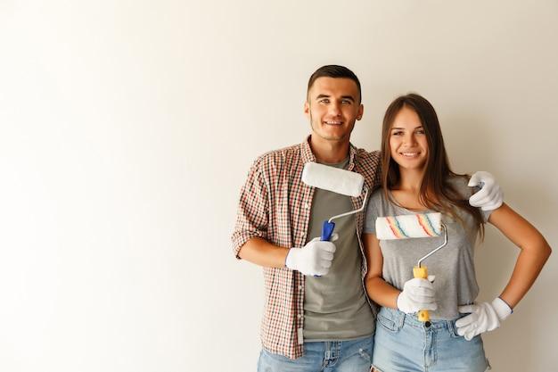 Casal feliz abraçando após reforma sua nova casa junto com rolo de pintura