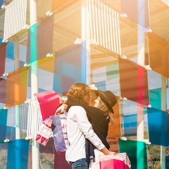 Casal feliz abraçando com sacos de compras nas mãos
