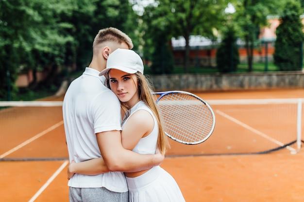 Casal feliz abraçando depois de jogar tênis, treinando juntos ao ar livre.