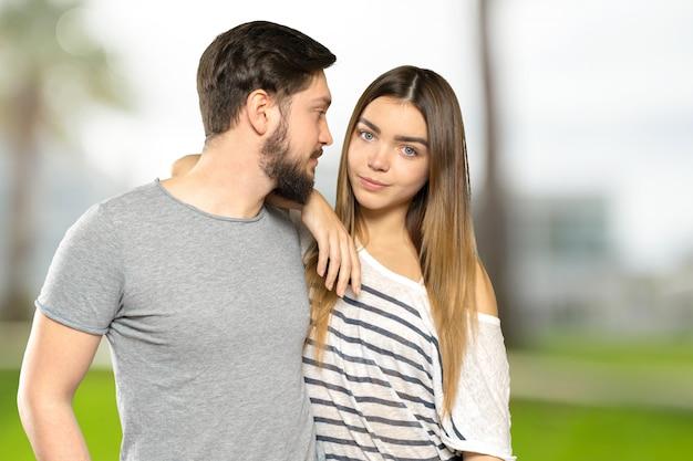 Casal feliz abraçando e olhando para a câmera