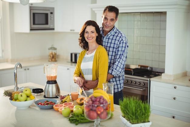 Casal feliz abraçando enquanto prepara batido na cozinha