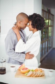 Casal feliz abraçando na cozinha em casa