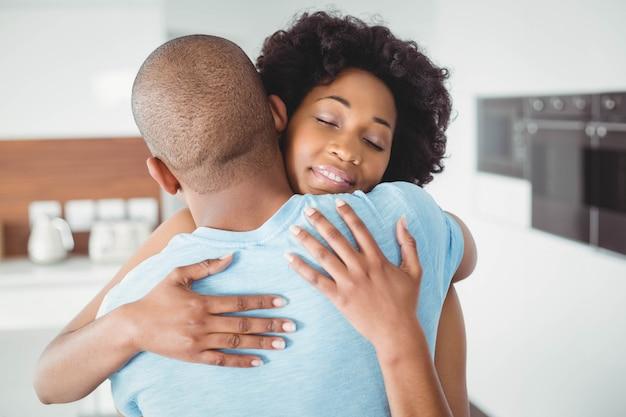 Casal feliz abraçando na cozinha