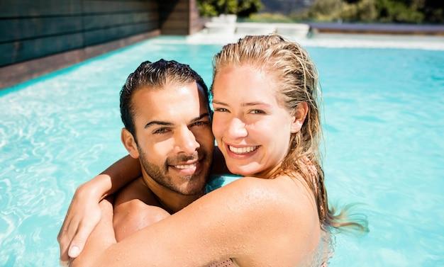 Casal feliz abraçando na piscina