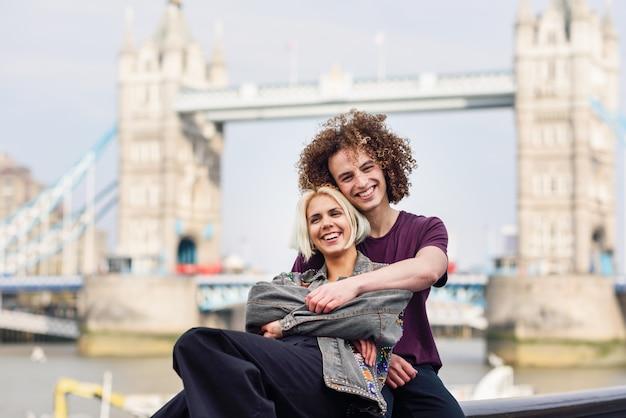Casal feliz abraçando na ponte da torre
