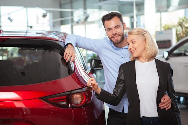 Casal feliz abraçando perto de seu carro novo na concessionária