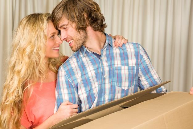 Casal feliz, abraçando-se com a caixa em movimento em casa