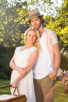 Casal feliz, abraçando-se com uma cesta de piquenique no jardim