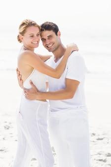 Casal feliz, abraçando-se na praia