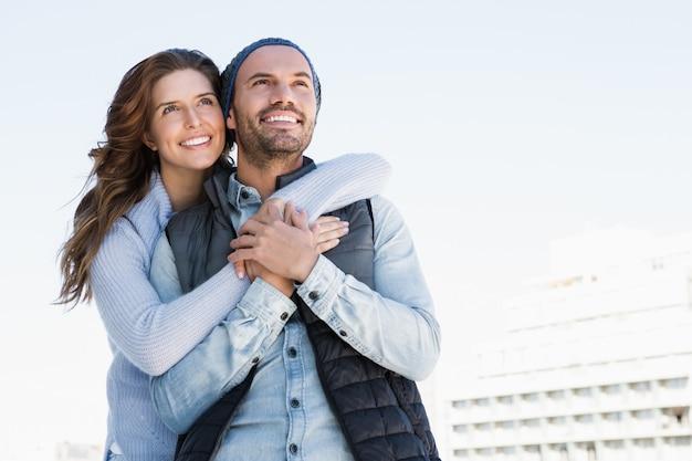 Casal feliz, abraçando uns aos outros e sorrindo ao ar livre