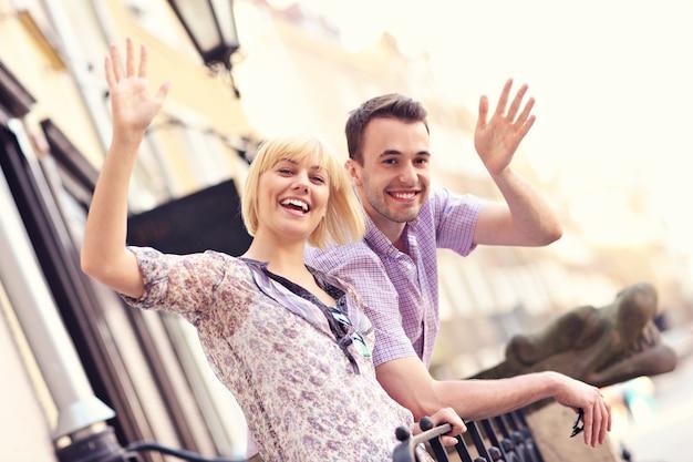 Casal feliz acenando para a câmera na cidade velha de gdansk, na polônia