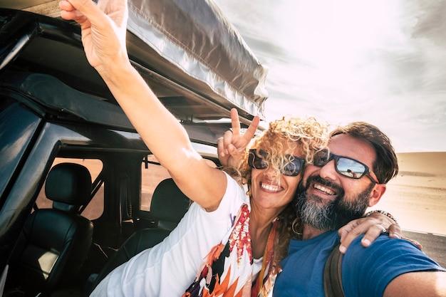 Casal feliz, alegre e sorridente no estilo de foto de selfie junto se abraçando com relacionamento e felicidade durante a viagem de carro - deserto e céu em backgorund - pessoas alegres nas férias de verão