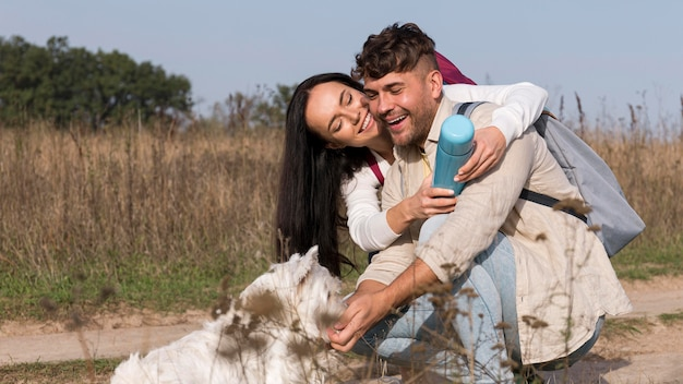 Casal feliz alimentando cachorro