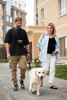 Casal feliz andando com o cachorro