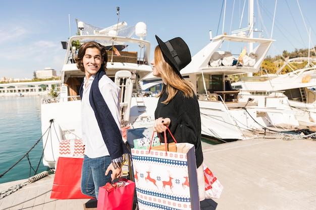 Casal feliz andando com sacolas de compras