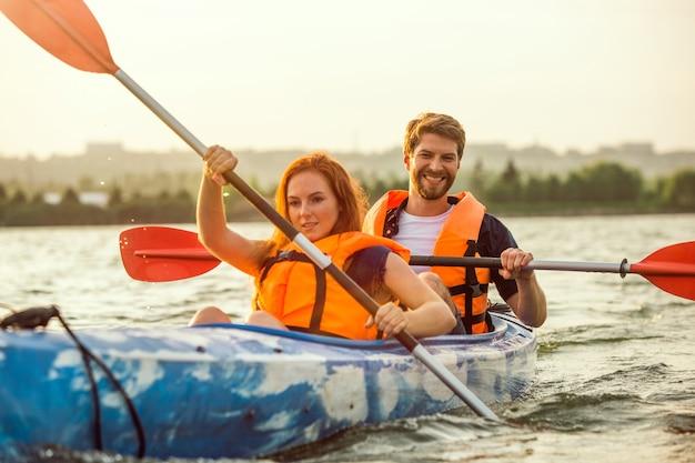 Casal feliz andando de caiaque no rio com o pôr do sol no fundo