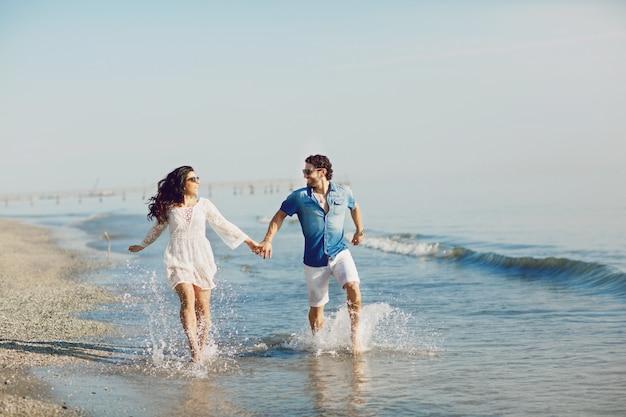 Casal feliz andando e brincando na praia