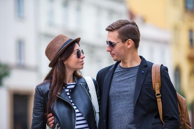 Casal feliz andando na europa. sorrindo amantes apreciando a paisagem urbana com monumentos famosos.