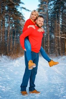 Casal feliz andando na floresta de neve