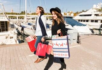 Casal feliz andando no cais com sacolas de compras